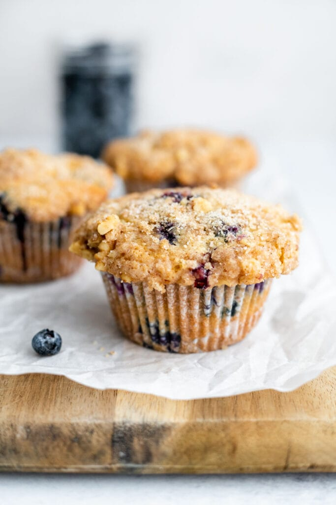 Three blueberry muffins resting on a cutting board in front of a jar of blueberries