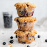 Stack of three blueberry muffins in front of a bowl of blueberries