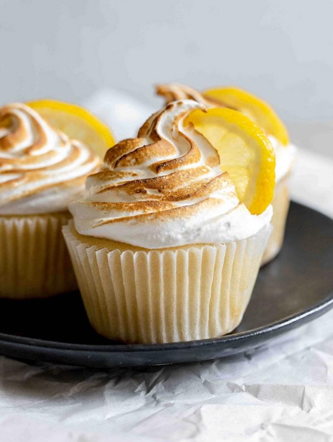 Three lemon meringue cupcakes on a plate