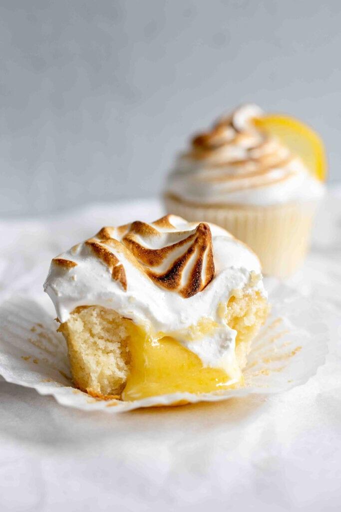 Opened lemon meringue cupcake with lemon curd falling out