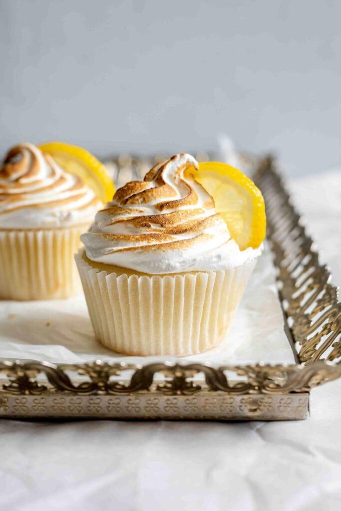 Two lemon meringue cupcakes on a gold platter