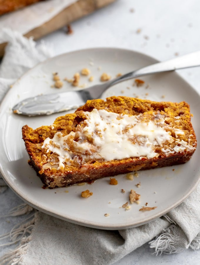 Slice of buttered pumpkin banana bread on a plate