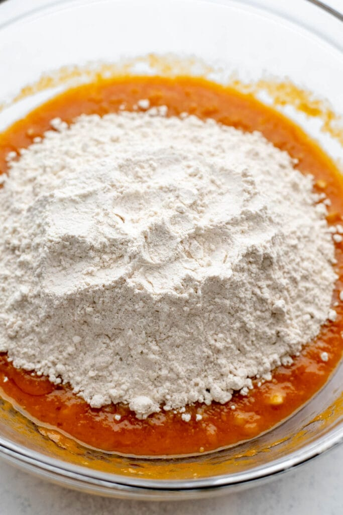 Adding dry ingredients into pumpkin banana bread batter