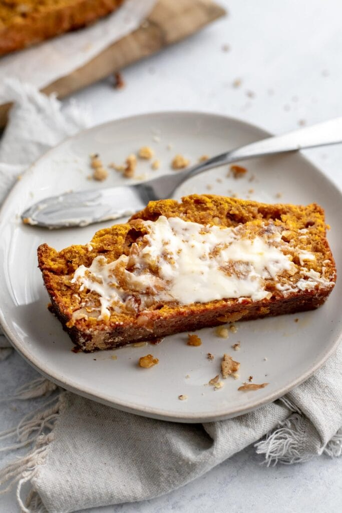 Slice of pumpkin banana bread slathered with butter on a plate