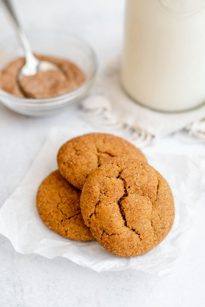 Three vegan gingerdoodles on a piece of parchment paper in front of a sugar mixture and milk