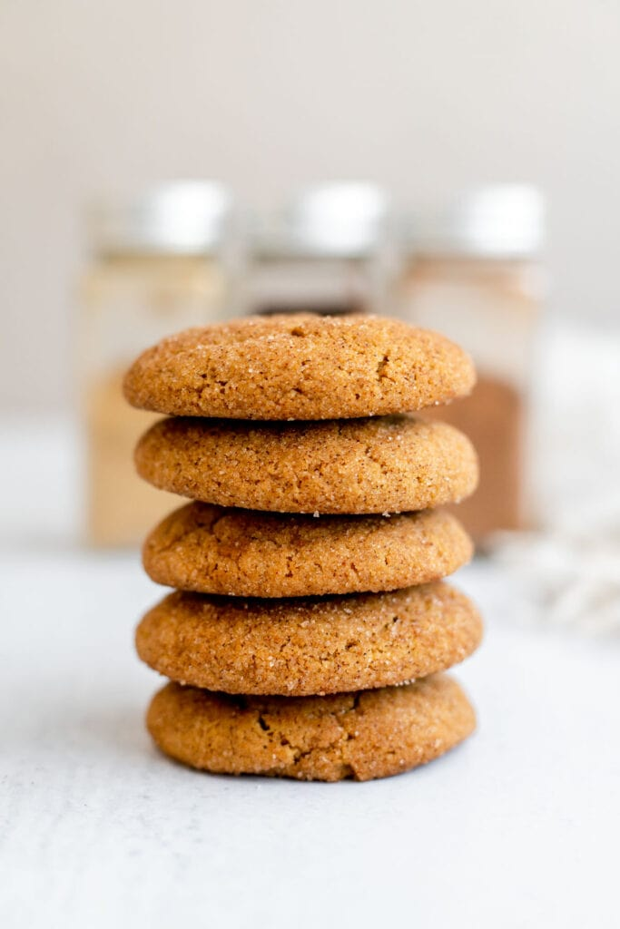 Stack of vegan gingerdoodles in front of jars of cinnamon, cloves, and ginger