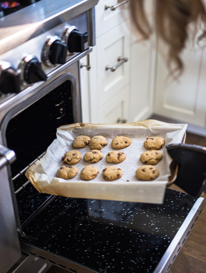 Woman putting a sheet tray of cookies into the oven