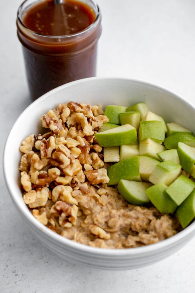 Bowl of oatmeal with apples and walnuts in front of a jar of caramel sauce